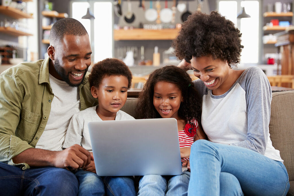 Photo of African American family on their computer smiling